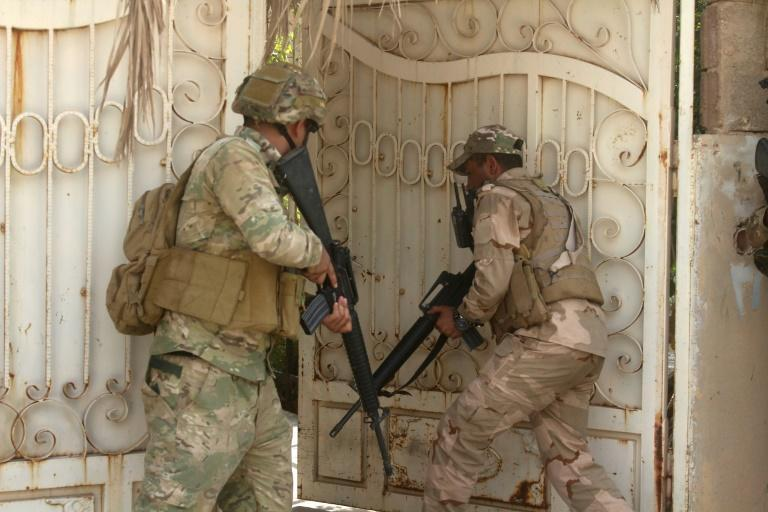 Iraqi troops storm a building in the town of Anna during the first phase of their drive up the Euphrates valley against the Islamic State group on September 22, 2017