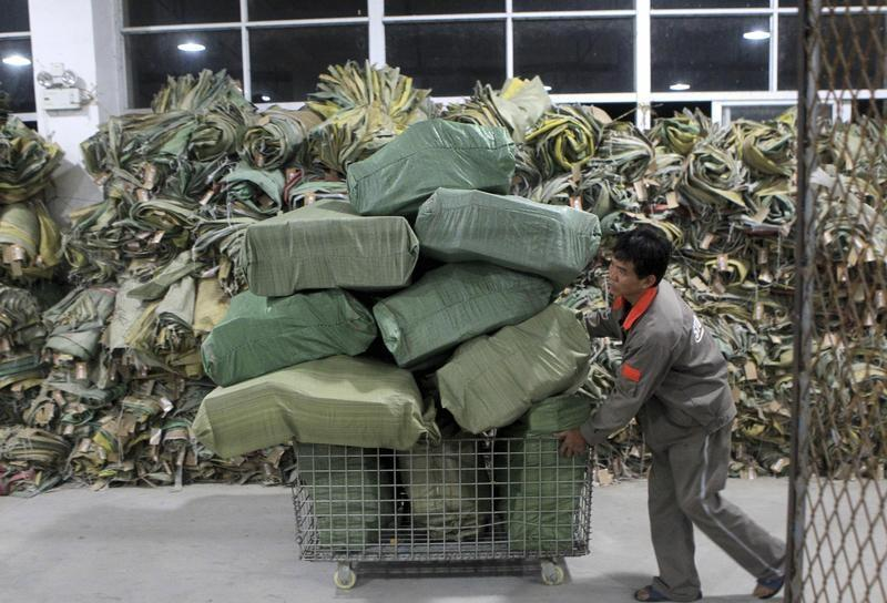 A worker pushes a cart filled with packages at a logistics hub in Fuzhou