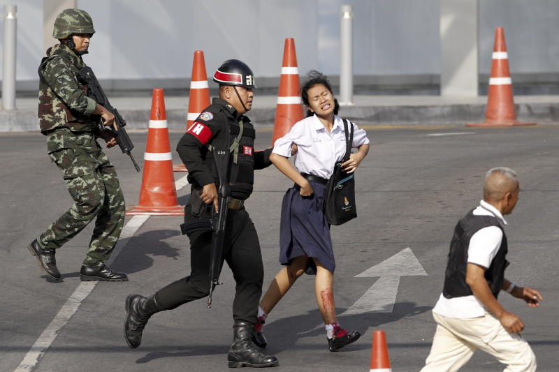 A woman with a bleeding leg is evacuated by soldiers during the tense standoff in Thailand.