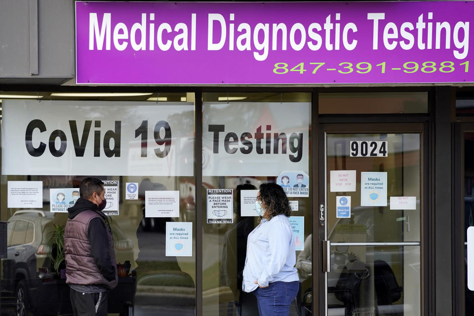 Exam Corp Lab employee, right, wears a mask as she talks with a patient lined up for COVID-19 testing in Niles, Ill., Wednesday, Oct. 21, 2020. (AP Photo/Nam Y. Huh)