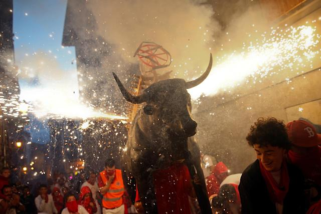 <p>Revelers run from the Fire Bull, a man carrying a bull figure packed with fireworks, at the San Fermin festival in Pamplona, northern Spain, July 13, 2017. (Photo: Susana Vera/Reuters) </p>