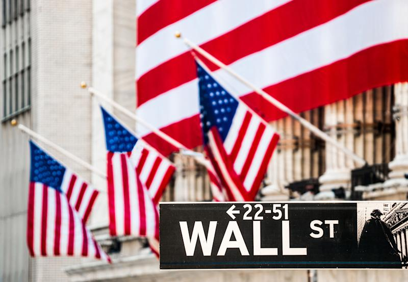 A large American flag covering the facade of the New York Stock Exchange, with the Wall St. street sign in the foreground.