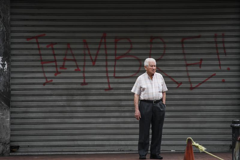CARACAS, MIRANDA, VENEZUELA - 2018/08/21: An elderly man seen standing next to a graffiti saying Hunger in the streets of Caracas. The opposition called for a general strike for one day as a protest against the new currency and the economic measures applied by Maduros Government. (Photo by Roman Camacho/SOPA Images/LightRocket via Getty Images)
