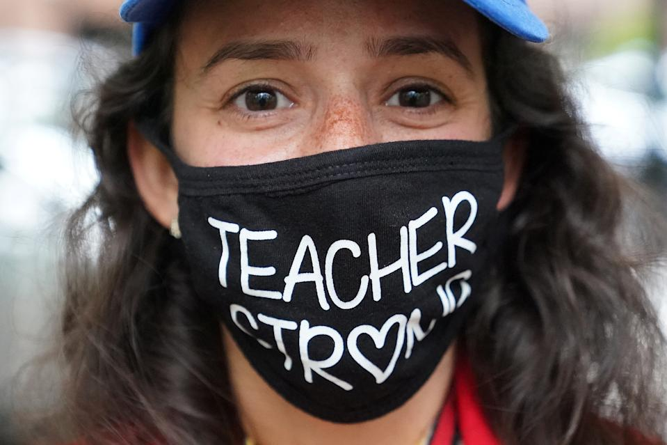 """A woman wears a """"Teacher Strong"""" face mask as she attends a rally to protest the opening of schools following the outbreak of the coronavirus disease (COVID-19) in the Brooklyn borough of New York City, New York, U.S., September 1, 2020.  REUTERS/Carlo Allegri"""