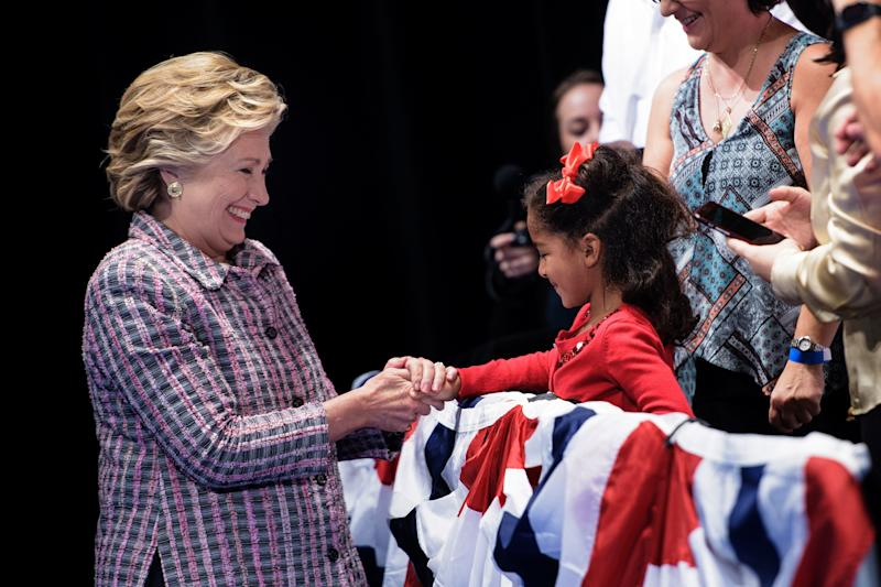 Hillary Clinton meets a child during her presidential run at the Sunrise Theatre in Fort Pierce, Florida.