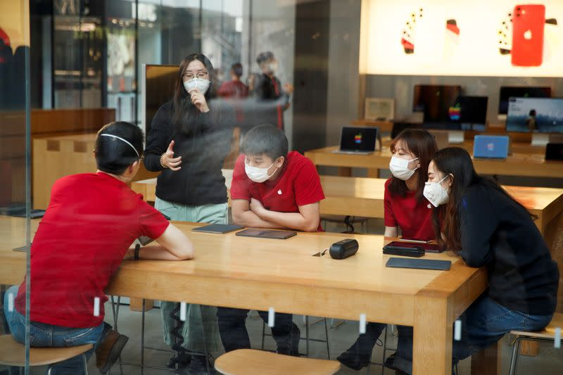 People wear face masks as they listen to a presentation in an Apple Store in the Sanlitun shopping district in Beijing