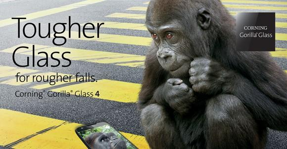 """A young gorilla sitting on a city street next to a smartphone with the caption """"Tougher Glass for rougher falls"""""""