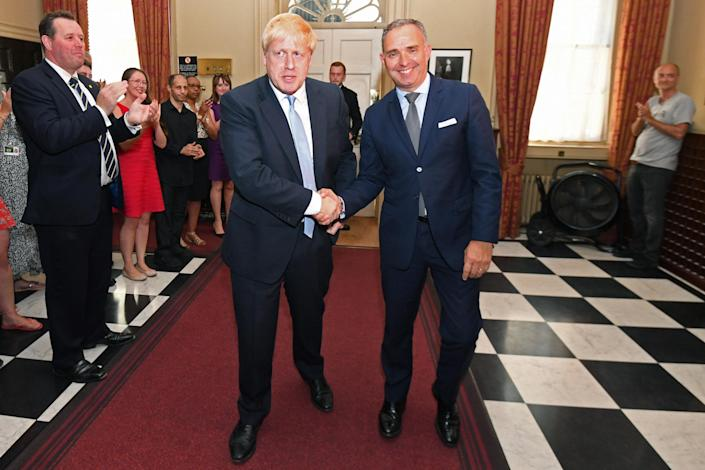 Boris Johnson shakes hands with Mark Sedwill as he is clapped into No 10 after winning the election last year: Getty