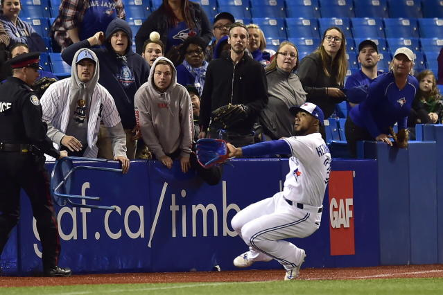Toronto Blue Jays right fielder Teoscar Hernandez slides into foul ball territory to make the catch for the out on New York Yankees' Brett Gardner during the 11th inning of a baseball game Wednesday, June 6, 2018, in Toronto. (Frank Gunn/The Canadian Press via AP)