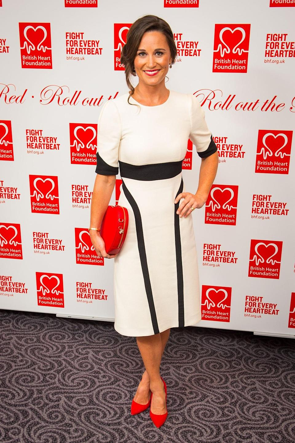 <p>Pippa paired a black and white Tabitha Webb dress with a birght red Radley clutch and matching heels for a charity event at the start of this year. <i>[Photo: PA Images]</i> </p>