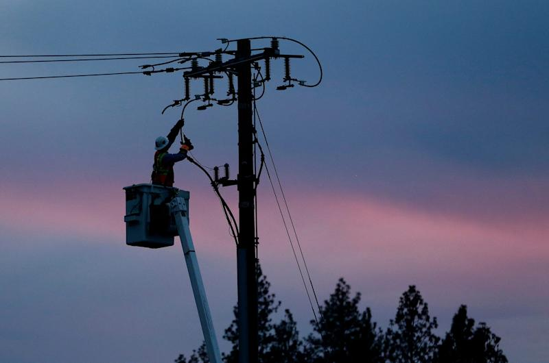 A Pacific Gas & Electric lineman works to repair a power line last November in fire-ravaged Paradise, Calif. The utility says power could be shut off in 30 counties in central and Northern California starting Wednesday, Oct. 9, when hot weather and strong winds are forecast, and through Thursday.