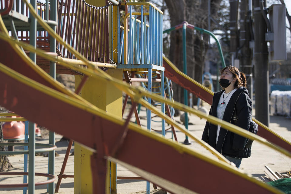 Hazuki Sato, a Futaba town official, visits a playground she used to play daily until she evacuated due to a nuclear scare following a 2011 earthquake, during an interview with The Associated Press in Futaba town, Fukushima prefecture, northeastern Japan, Sunday, Feb. 28, 2021. She's now preparing for the coming-of-age ceremony that is typical for Japanese 20-year-olds, hoping for a reunion in town so she can reconnect with her former classmates who have scattered. (AP Photo/Hiro Komae)