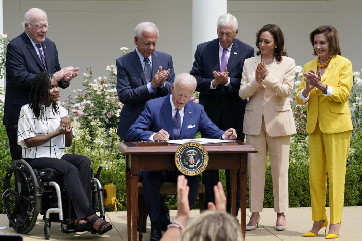 President Joe Biden, center, signs a proclamation during an event in the Rose Garden of the White House in Washington, Monday, July 26, 2021, to highlight the bipartisan roots of the Americans with Disabilities Act and marking the law's 31st anniversary. Biden is joined by, from left, Sen. Patrick Leahy, D-Vt., artist Tyree Brown, former Rep. Tony Coelho, D-Calif, House Minority Whip Steny Hoyer, D-Md., Vice President Kamala Harris, and House Speaker Nancy Pelosi of California. (AP Photo/Susan Walsh)