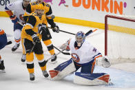 New York Islanders goaltender Ilya Sorokin (30) watches the puck with Pittsburgh Penguins' Bryan Rust (17) looking for a deflection during the first period in Game 5 of an NHL hockey Stanley Cup first-round playoff series in Pittsburgh, Monday, May 24, 2021. (AP Photo/Gene J. Puskar)