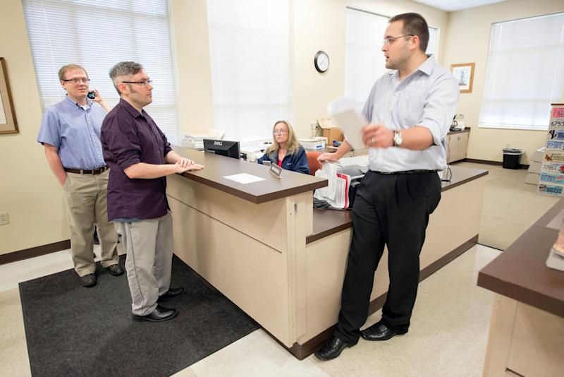 David Ermold (left) and his husband, David Moore (center), were among the couples who were denied marriage licenses by Kim Davis in 2015.