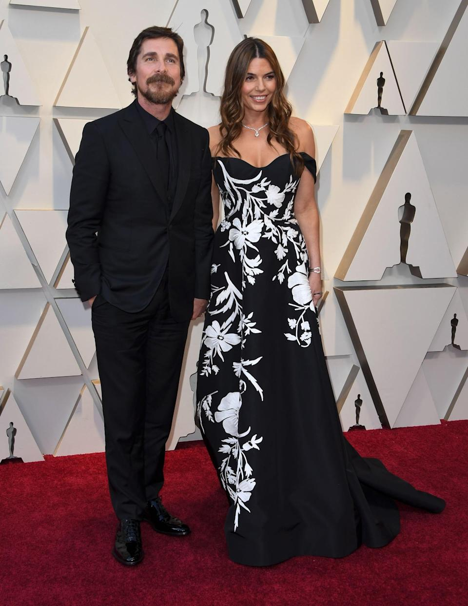 <p>Christian is wearing an all-black suit with Cartier jewels and Tod's shoes, and Sibi is wearing an off-the-shoulder black and white gown.</p>