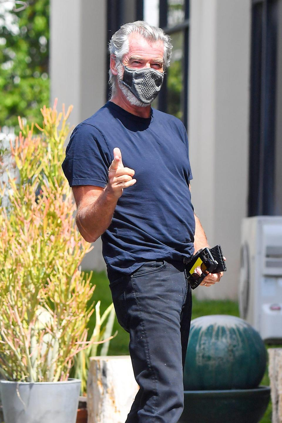 <p>Pierce Brosnan gets playful with the cameras on Sunday while arriving to a studio in L.A. </p>