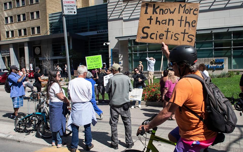 """Healthcare workers staged a counter protest. One held a sign saying """"I know more than the scientists"""" - Chris Young/The Canadian Press via AP"""
