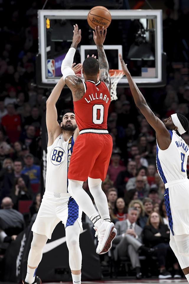 Portland Trail Blazers guard Damian Lillard, center, hits a shot over Indiana Pacers center Goga Bitadze, left, and Indiana Pacers forward Justin Holiday, right, during the first half of an NBA basketball game in Portland, Ore., Sunday, Jan. 26, 2020. (AP Photo/Steve Dykes)