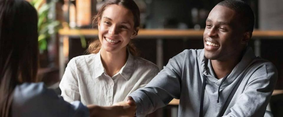 Happy young interracial couple shake hand of bank manager broker