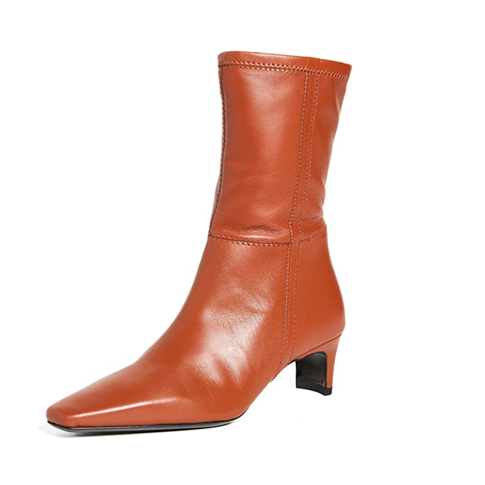 """These sleek leather boots bring the ~drama~ with a slightly pointed toe, mid-calf height, and totally reasonable kitten heel. $450, Amazon. <a href=""""https://www.amazon.com/STAUD-Womens-Boots-Orange-Medium/dp/B09B48C3MS"""" rel=""""nofollow noopener"""" target=""""_blank"""" data-ylk=""""slk:Get it now!"""" class=""""link rapid-noclick-resp"""">Get it now!</a>"""