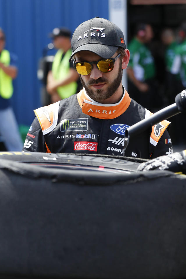 Daniel Suarez looks at his tire damage during practice for a NASCAR Cup Series auto race at Michigan International Speedway in Brooklyn, Mich., Saturday, Aug. 10, 2019. (AP Photo/Paul Sancya)