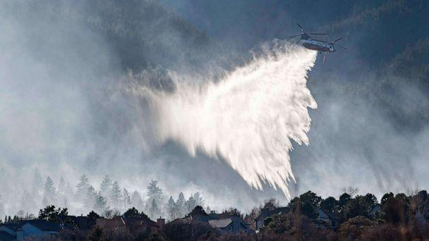 PHOTO: A Chinook helicopter drops water on a wildfire near Bear Creek Regional Park on the westside of Colorado Springs, Colo., Thursday, Nov. 19, 2020. (Christian Murdock/AP)