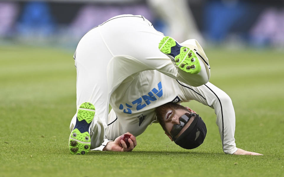 New Zealand's Kane Williamson rolls on the ground after taking a catch to dismiss the West Indies' John Campbell during play on day three of their first cricket test in Hamilton, New Zealand, Saturday, Dec. 5, 2020. (Andrew Cornaga/Photosport via AP)