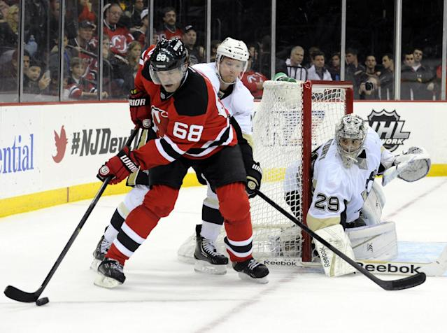 New Jersey Devils' Jaromir Jagr (68), of Czech Republic, handles the puck as he is checked by Pittsburgh Penguins' Matt Niskanen as Penguins goaltender Marc-Andre Fleury, right, guards the net during the second period of an NHL hockey game Saturday, Nov. 16, 2013, in Newark, N.J. (AP Photo/Bill Kostroun)