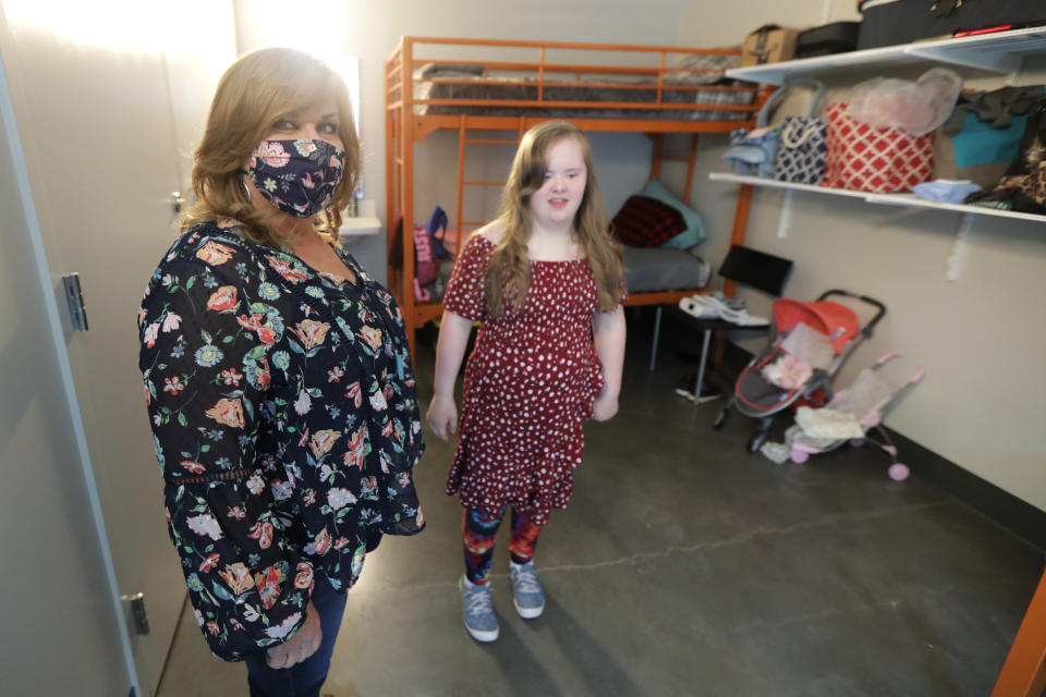 Connie Wade, left, poses for a photo with her daughter Emilyanne, 12, Wednesday, June 17, 2020, in their room at Mary's Place, a family homeless shelter located inside an Amazon corporate building on the tech giant's Seattle campus. The facility is home to the Popsicle Place shelter program, an initiative to address the needs of homeless children with life-threatening health conditions. (AP Photo/Ted S. Warren)