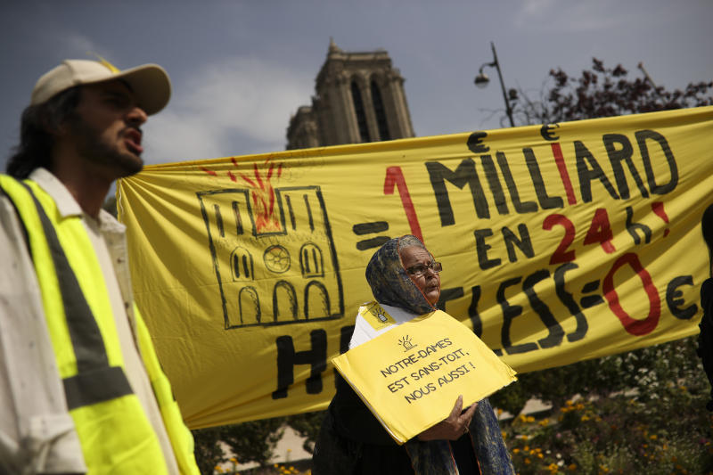 "People shout slogans during a protest in front of the Notre Dame cathedral in Paris, Monday, April 22, 2019. The yellow placard and banner reads in French: ""One billion in 24 hours! Homeless Zero"" and ""Notre-Dame is roofless, we too!"". (AP Photo/Francisco Seco)"