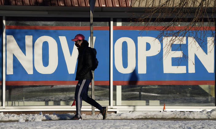 FILE - In this Feb. 25, 2021, file photo, a pedestrian in a face covering walks past the sign plastered on the windows of a restaurant to announce that it is open after closure because of the coronavirus in Boulder, Colo. While most Americans have weathered the pandemic financially, about 38 million say they are worse off now than before the outbreak began in the U.S. According to a new poll from Impact Genome and The Associated Press-NORC Center for Public Affairs Research 55% of Americans say their financial circumstances are about the same now as a year ago, and 30% say their finances have improved. (AP Photo/David Zalubowski, File)