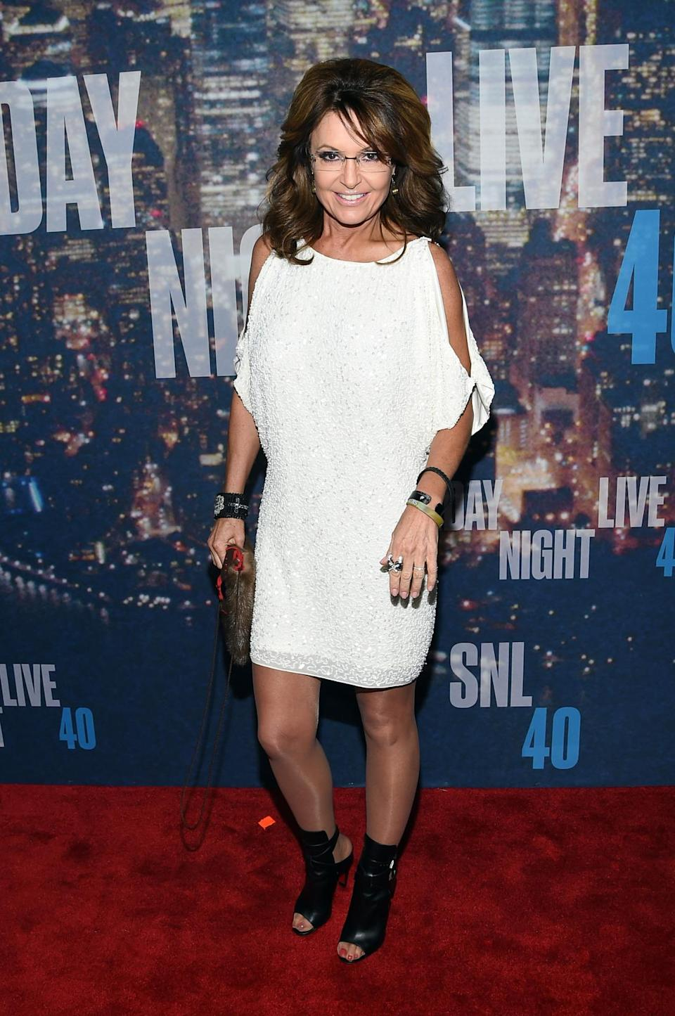 Sarah Palin traded her politician power suits and Alaskan snowsuits for a short white dress and open-toed booties.