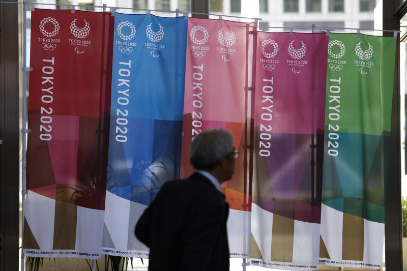 A man walks past the Tokyo 2020 banners at the Tokyo Metropolitan Government building Thursday, Nov. 21, 2019, in Tokyo. The French language has been almost invisible during the drawn-out preparations for next year's Tokyo Olympics. (AP Photo/Jae C. Hong)