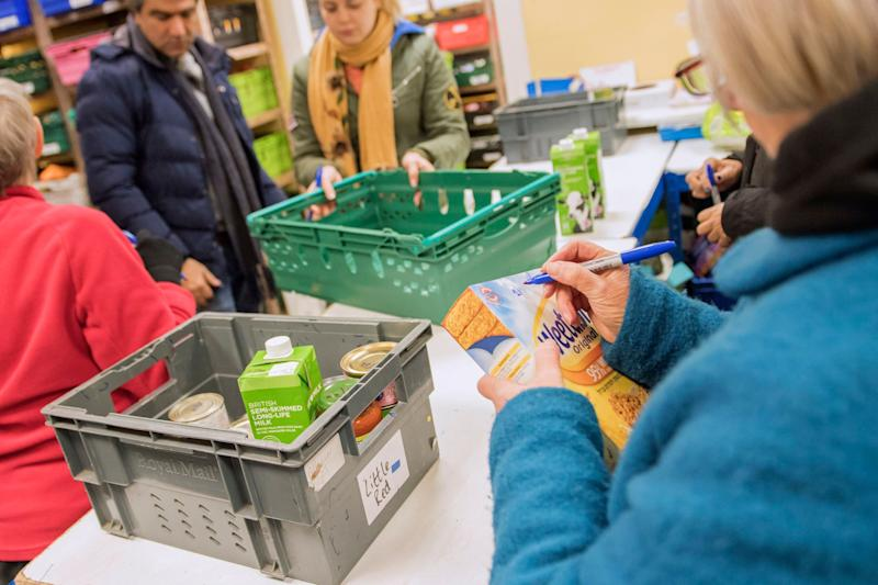 Foodbank volunteers sort through donations at a warehouse. (Photo: Anthony Devlin via Getty Images)