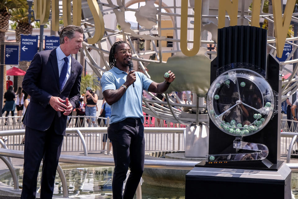 California Governor Gavin Newsom, left, looks on as Access Hollywood personality Scott Evans draws a ball with a winning number during the Vax for the Win lottery contest at Universal Studios in Universal City, Calif., Tuesday, June 15, 2021. Starting Tuesday, there were no more state rules on social distancing, and no more limits on capacity at restaurants, bars, supermarkets, gyms, stadiums or anywhere else. (AP Photo/Ringo H.W. Chiu)