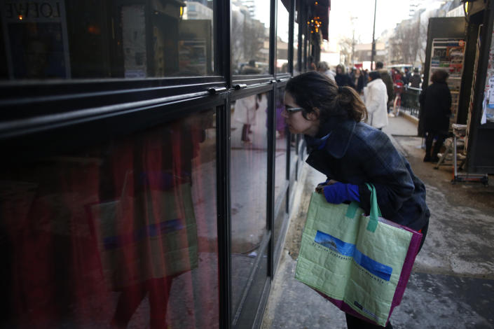 A woman looks inside the restaurant La Rotonde, in Paris, Saturday, jan.18, 2020. The Paris prosecutor's office says it has opened an investigation to determine the causes of the Rotonde fire. (AP Photo/Thibault Camus)