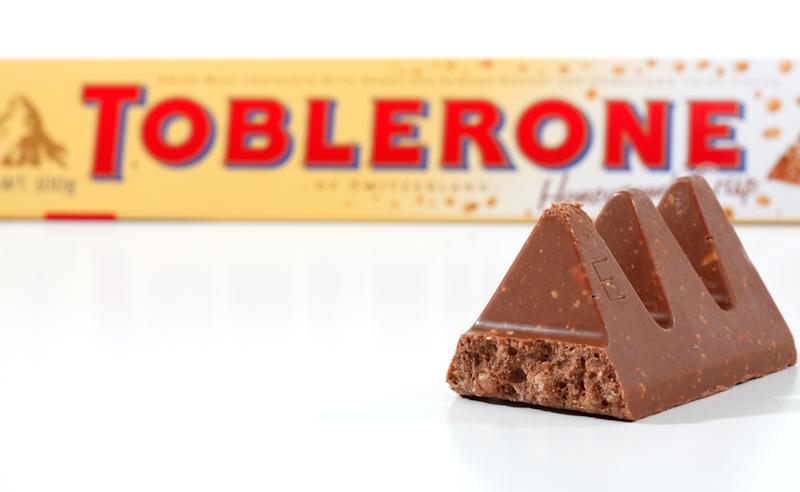 """Penrith, Australia - February 25, 2011: 100g Toblerone chocolate bar (2155kj) containing honey and almond nougat, cristpy rice and chocolate, made in Switzerland for Kraft Foods. Packaging at rear with pieces of the chocolate bar in focus in the foreground. Photographed in studio on white background."""