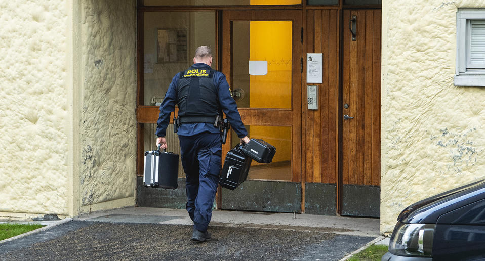 A police officer walks into the apartment building where the man was found.