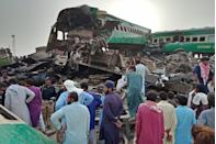 <p>Local residents gather to observe the crash site after two trains (one passenger and the other commercial) collided in Pakistan. 11 people were killed and around 80 people were injured.</p>