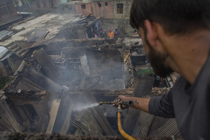 A Kashmiri villager sprays water on burning debris before clearing a house destroyed in a gunfight in Pulwama, south of Srinagar, Indian controlled Kashmir, Wednesday, July 14, 2021. Three suspected rebels were killed in a gunfight in Indian-controlled Kashmir on Wednesday, officials said, as violence in the disputed region increased in recent weeks. Two residential houses were also destroyed. (AP Photo/ Dar Yasin)