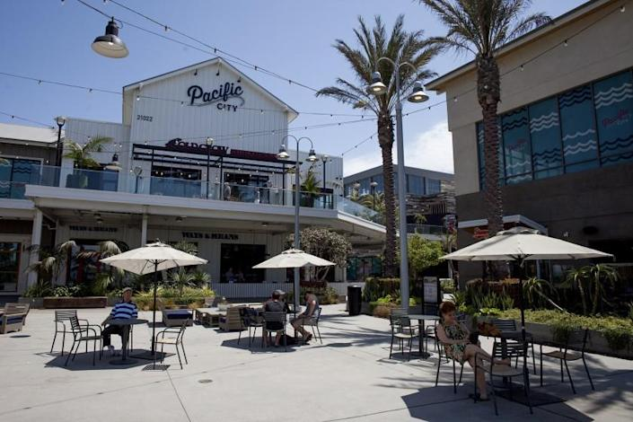 """People sit outside restaurants at Pacific City in Huntington Beach in this 2016 file photo. Bluegold/LSXO, a restaurant in the outdoor mall, said Monday it was closing for deep cleaning amid the coronavirus crisis. <span class=""""copyright"""">(Kevin Chang / Times Community News)</span>"""