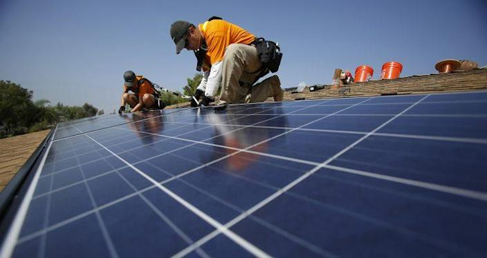 Vivint Solar technicians install solar panels on the roof of a house in Mission Viejo, Calif., in2013.