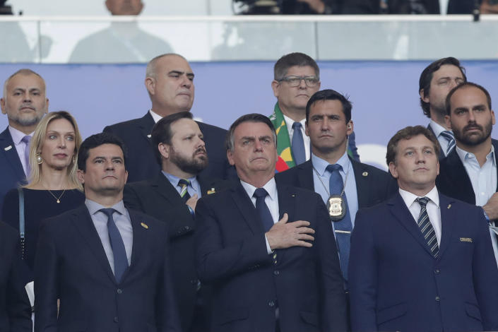 President Jair Bolsonaro, center, sings the national anthem next Brazil's Justice Minister Sergio Moro, left, and Conmebol President Alejandro Dominguez, right, prior to the final soccer match of the Copa America between Brazil and Peru at the Maracana stadium in Rio de Janeiro, Brazil, Sunday, July 7, 2019. (AP Photo/Andre Penner)