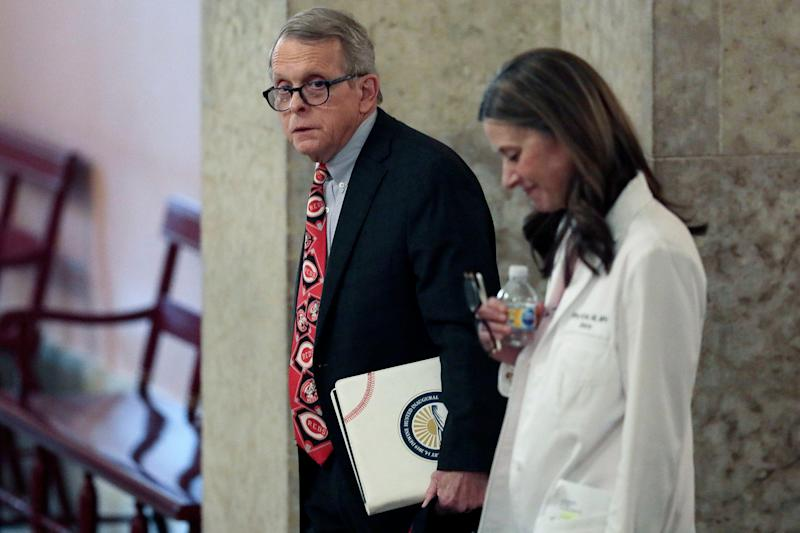 Ohio Gov. Mike DeWine and Dr. Amy Acton, director of the Ohio Department of Health, prepare to deliver a daily coronavirus briefing on March 26, 2020, in Columbus.