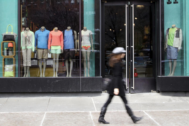 FILE - In this Tuesday, March 19, 2013 file photo,  a woman walks past the Lululemon Athletica store at Union Square in New York. Lululemon says no demonstrations of yoga positions or otherwise are needed to return its pricey black yoga pants that the company pulled from shelves for being too sheer. The yoga gear maker's policy statement comes after a New York Post report that was widely circulated by the media recounted one woman's tale of being asked to bend over when trying to return some pants to prove they were sheer. (AP Photo/Mary Altaffer)