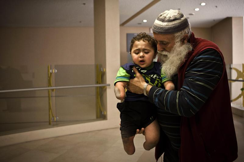 "In this Monday, April 29, 2013 photo, Palestinian Hamouda Al-Farra, holds his grandson Mohammed in the Tel Hashomer Hospital near Ramat Gan, central Israel. Abandonment, generosity and tragedy have each shaken Mohammed al-Farra's life since he was born in the southern Gaza Strip town of Khan Younis three and a half years ago with a rare genetic disorder that crippled his bowels, weakened his immune system and caused an infection that destroyed his hands and feet. His parents abandoned him and the Palestinian government won't pay for his care. But his grandfather has raised him instead, and Israeli doctors privately fundraise to cover his medical costs. As a result, the Palestinian toddler calls his grandfather ""daddy,"" he babbles in a mix of Hebrew and Arabic and the only home he has ever known is the yellow-painted children's ward. (AP Photo/Dan Balilty)"