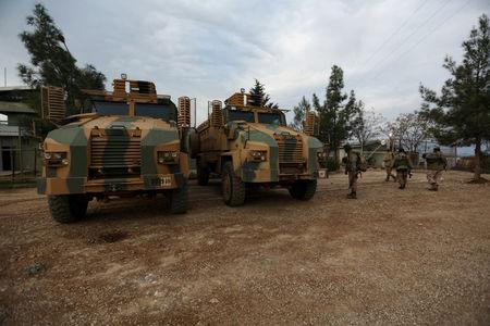 Turkish-backed Free Syrian Army fighters are seen next to military trucks in Northern Afrin countryside, Syria, February 16, 2018. REUTERS/Khalil Ashawi