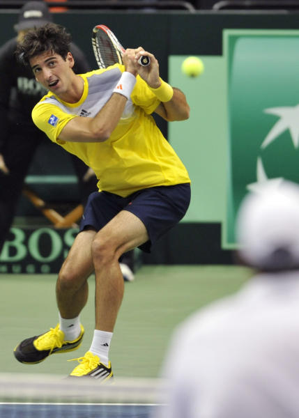 Brazil's Thomaz Bellucci returns a shot from the USA's John Isner in the first match of the day during the 2013 World Group First Round of the Davis Cup Sunday Feb. 3, 2013 at Veterans Memorial Arena in Jacksonville, Florida. (AP Photo/The Florida Times-Union, Will Dickey)
