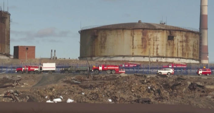 In this image taken from video provided by the RU-RTR Russian television on Wednesday, June 3, 2020, Russian Emergency Situations Ministry trucks work at the scene of an oil spill at a power plant in an outlying section of the city of Norilsk, 2900 kilometers (1800 miles) northeast of Moscow, Russia. Russian President Vladimir Putin has declared a state of emergency in a region of Siberia after an estimated 20,000 tons of diesel fuel spilled from a power plant storage facility and fouled waterways. (RU-RTR Russian Television via AP)